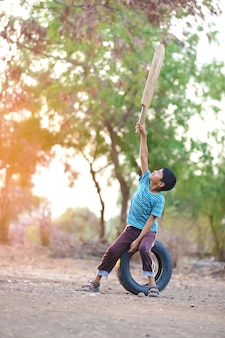 Enfant indien rural jouant au cricket