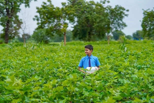 Enfant indien tenant une tirelire au champ de l'agriculture verte.