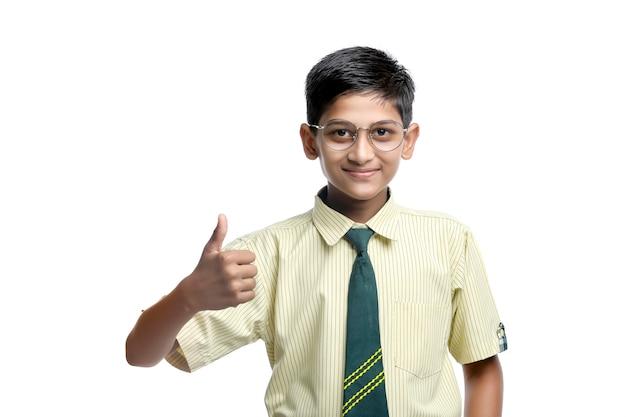 Enfant indien en uniforme scolaire et montrant des coups sur fond blanc.