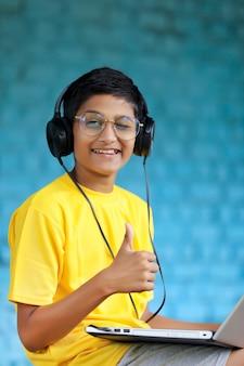 Enfant indien utilisant un casque et montrant des coups de poing