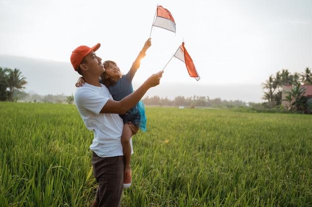 Enfant indonésien avec père jouer avec le drapeau national