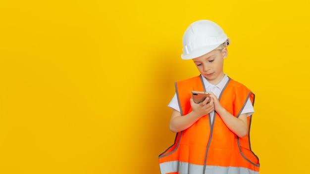 Un enfant ingénieur constructeur vêtu d'un gilet réfléchissant et d'un casque de chantier