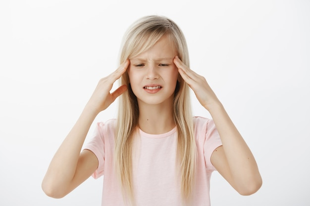 L'enfant inquiet non focalisé ne peut pas penser clairement et garder l'information à l'esprit. inquiète jeune fille confuse aux cheveux blonds, tenant les mains sur les tempes et grimaçant, essayant de se souvenir de quelque chose
