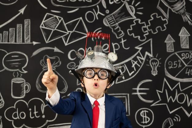 L'enfant intelligent fait semblant d'être des hommes d'affaires. enfant drôle portant un casque avec ampoule. concept d'idée d'éducation, d'intelligence artificielle et d'entreprise