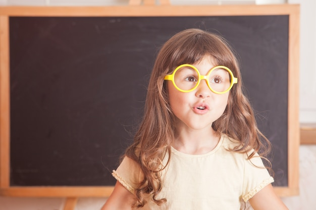 Un enfant intelligent portant des lunettes jaunes se tenait devant un tableau noir
