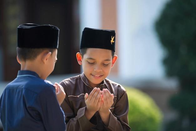 Un enfant islamique prie pour étudier avec sa sœur et son frère dans une mosquée de songkhla, en thaïlande.