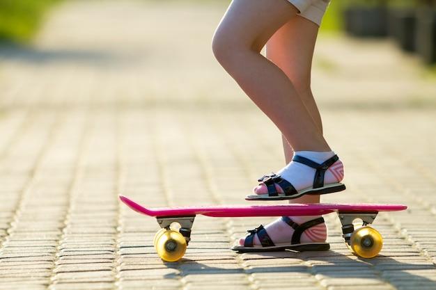 Enfant jambes minces en chaussettes blanches et sandales noires sur planche à roulettes rose en plastique