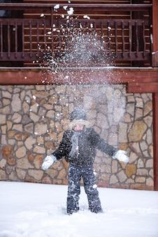 Un enfant jette de la neige en hiver