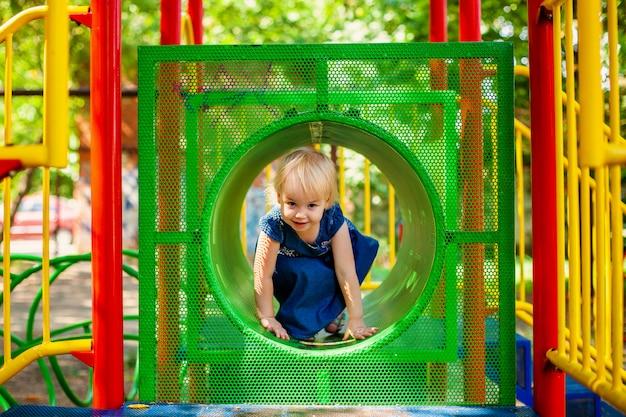 Enfant jouant sur une aire de jeux extérieure. petite fille joue sur le jardin de l'école ou de la maternelle