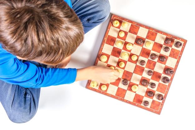 Enfant jouant au jeu d'échecs sur l'échiquier