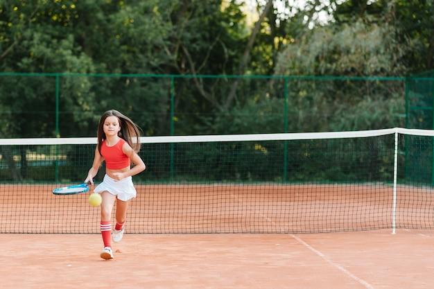 Enfant jouant au tennis sur un court extérieur. petite fille avec raquette de tennis et balle au club de sport. exercice actif pour les enfants