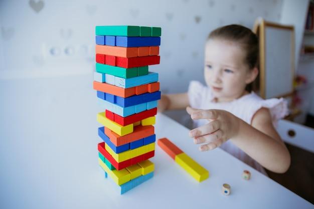 Enfant jouant avec des briques en bois colorées sur le fond de la table blanche