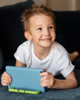 Enfant jouant sur le canapé sur smartphone