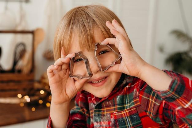 Enfant jouant avec des cookies de forme