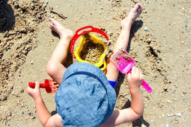 Enfant jouant avec du sable, une pelle, un seau