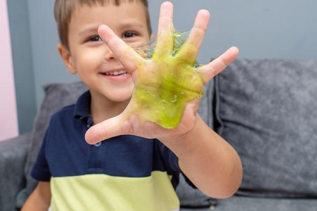 Enfant jouant avec du slime de couleur rouge, du gunge, du gel dans les mains