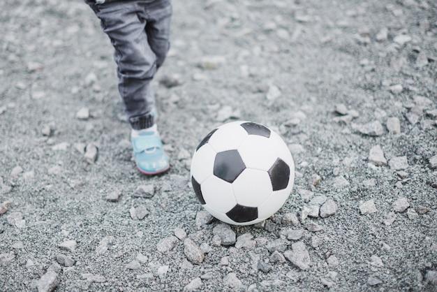 Enfant jouant à l'extérieur avec le football