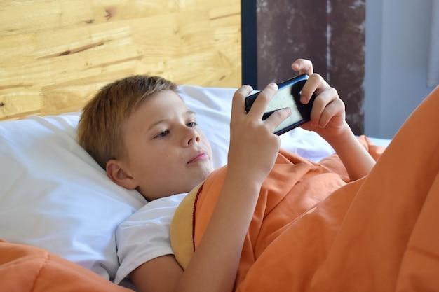 Enfant jouant à des jeux dans le téléphone.