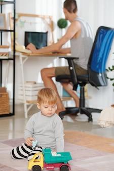 Enfant jouant avec des jouets avec son père travaillant sur ordinateur en arrière-plan à la maison