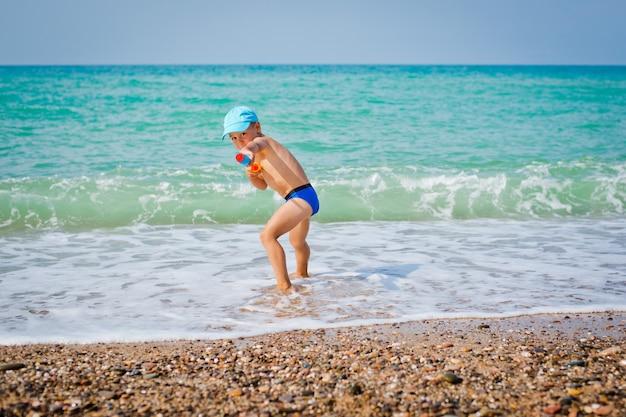 Enfant jouant en mer avec pistolet à eau