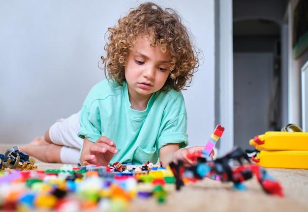 Enfant jouant avec des morceaux d'empilement sur un tapis à l'intérieur d'une maison