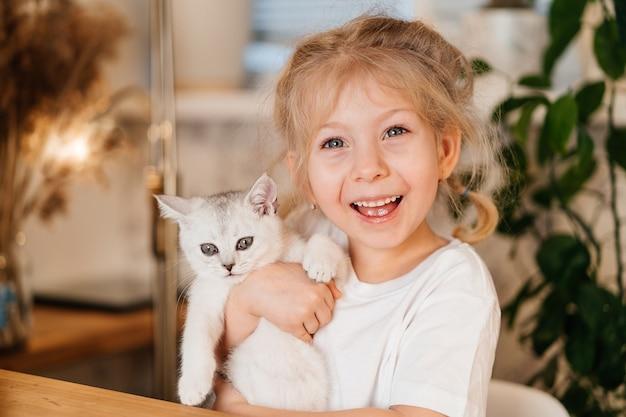 Enfant jouant avec petit chat. une petite fille tient un chaton blanc. une petite fille se blottit contre un animal mignon.