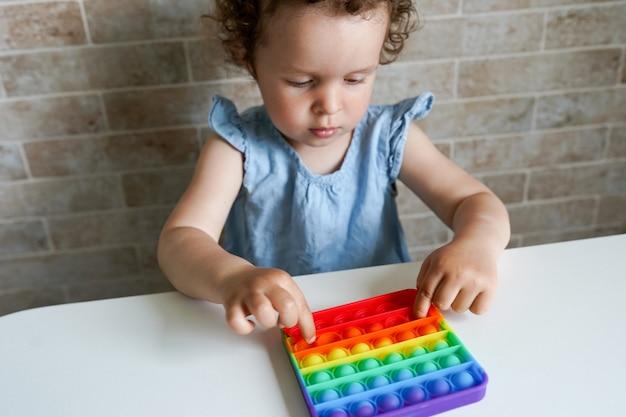 Enfant jouant poppit fidget toy. jeune petite fille à la maison tenant pop it new fidget toy, populaire auprès des enfants, les aide à se concentrer.