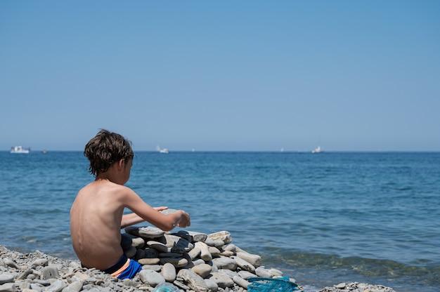 Enfant jouant avec de la roche sur la plage par une belle journée ensoleillée.