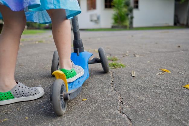 Enfant jouant avec scooter, activité pour enfant, terrain de jeu, plein air