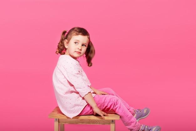 Enfant jouant le singe. petite fille portant des vêtements roses contre un rose
