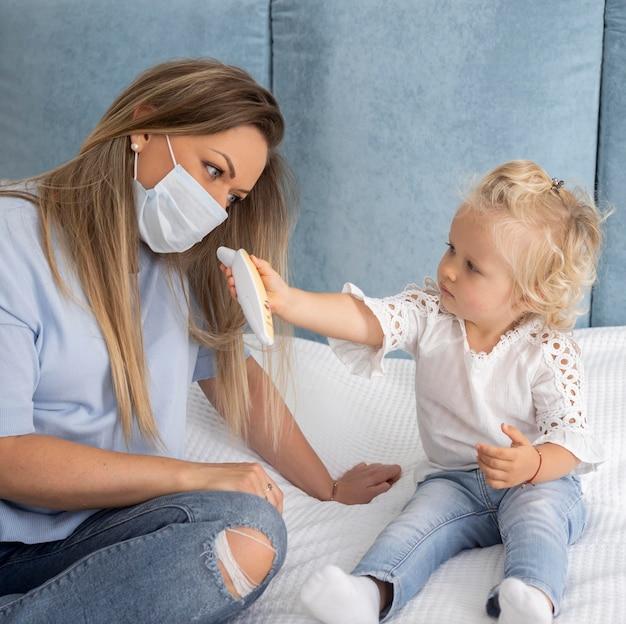Enfant jouant avec un thermomètre à côté de maman