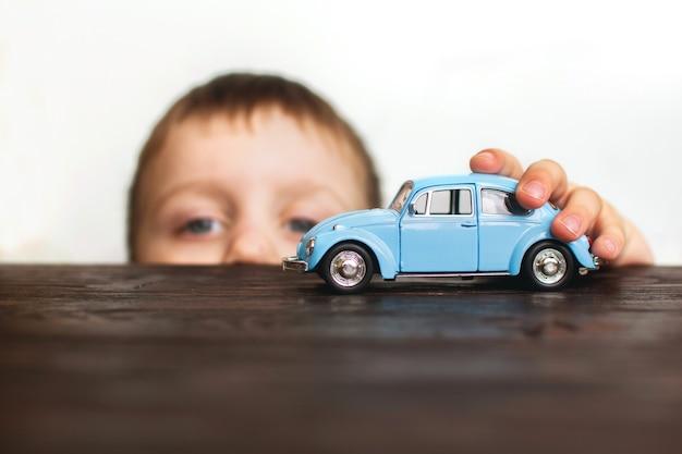 Enfant jouant avec la voiture à proximité sur un fond blanc