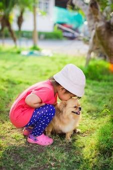 L'enfant joue avec un chien. les enfants qui vivent avec un animal de compagnie semblent avoir de meilleures aptitudes sociales.