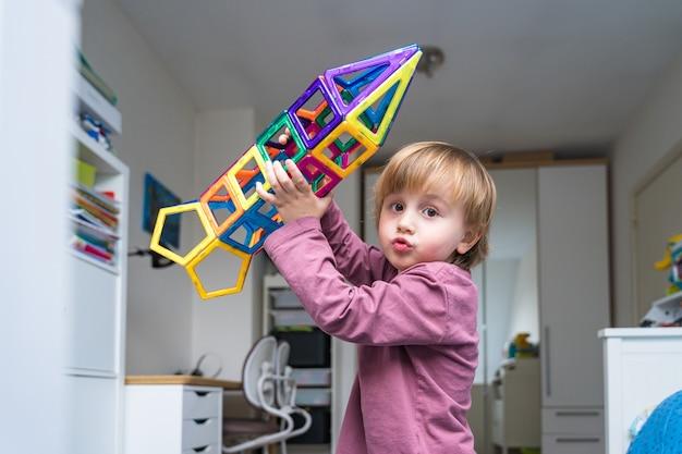 L'enfant joue avec un constructeur magnétique dans sa chambre