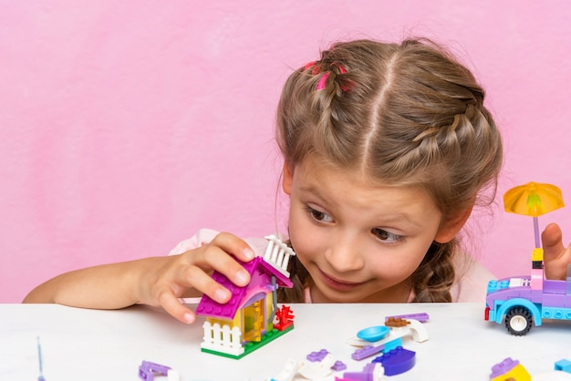 L'enfant joue avec des cubes colorés et en construit des figurines.