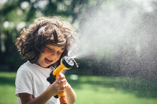 L'enfant joue avec de l'eau dans la cour dans le jardin