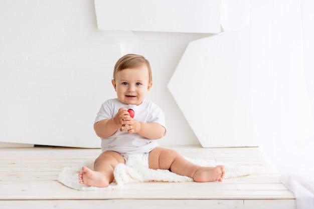 L'enfant joue, heureux petit bébé mignon de six mois dans un t-shirt blanc et des couches est assis sur un fond clair à la maison et joue, place pour le texte