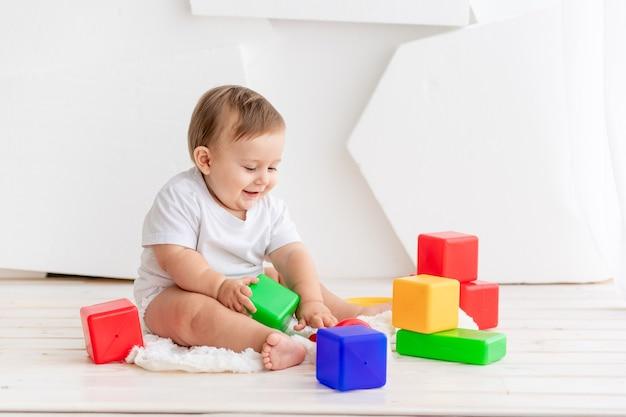 L'enfant joue, heureux petit bébé de six mois dans un t-shirt blanc et des couches jouant à la maison sur un tapis dans une pièce lumineuse avec des cubes de couleurs vives