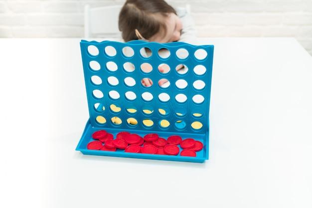 L'enfant joue à un jeu de société. l'enfant a perdu le jeu et est triste