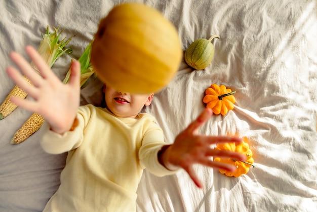 L'enfant joue à la maison sur le lit avec une citrouille