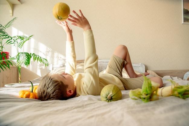 L'enfant joue à la maison sur le lit avec des citrouilles