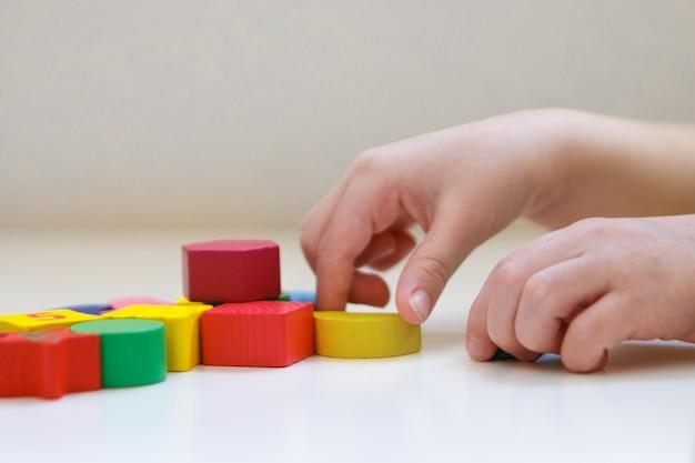 L'enfant joue avec des personnages colorés. détails du jouet dans les mains.