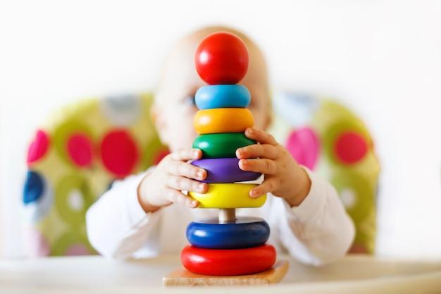 L'enfant joue la pyramide enfant jouant avec des jouets en bois