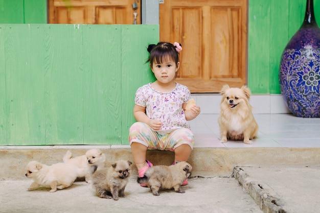 Un enfant joue avec son chien et son chiot. les enfants qui vivent avec des animaux semblent avoir une plus grande