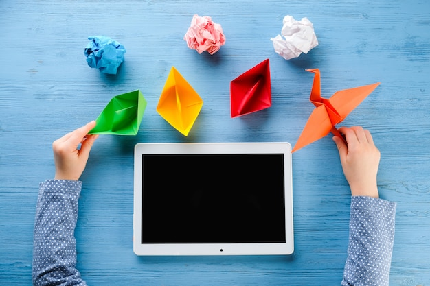 Enfant joue avec tablette et papier origami sur une table bleue
