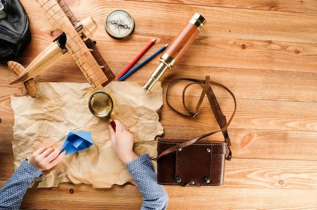 L'enfant joue un voyage avec une carte et une loupe