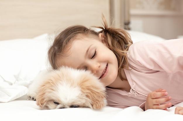 Enfant jouer bébé doggirl et chiot chien dormir sur lit à homeanimal carefriendship personnes et animal de compagnie