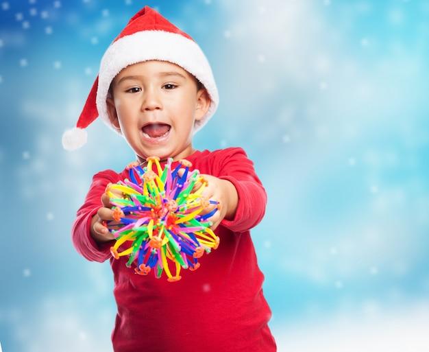 Enfant avec un jouet et la bouche ouverte