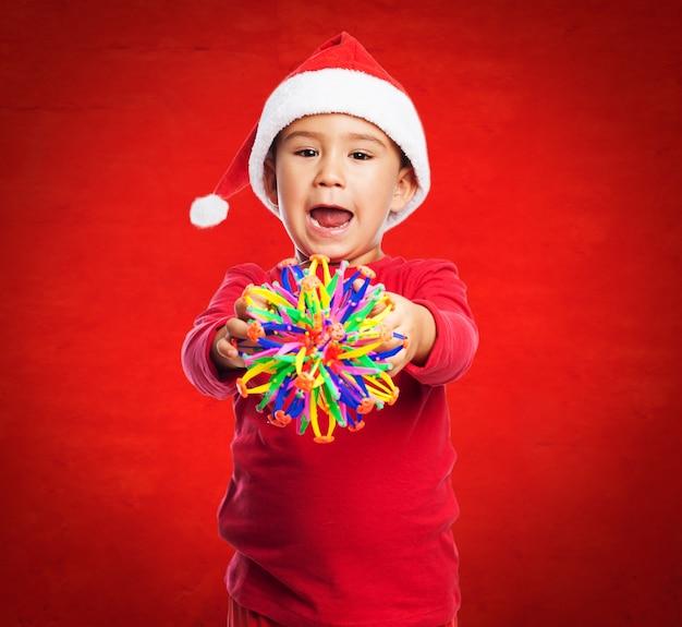 Enfant avec un jouet dans un fond rouge