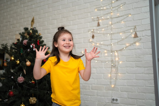 Un enfant joyeux attrape des guirlandes. des vacances d'enfants lumineuses. un enfant vêtu d'un t-shirt jaune attrape une serpentine.